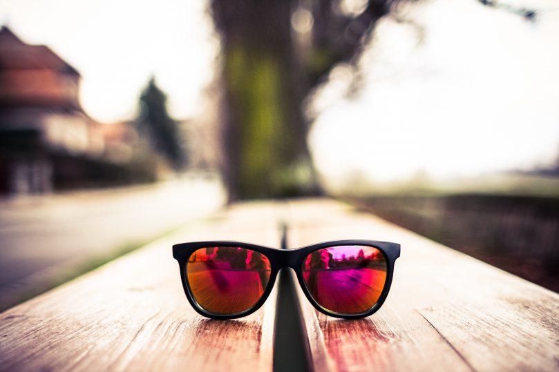 Roze bril op een bankje