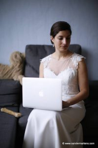 Woman typing in her wedding dress